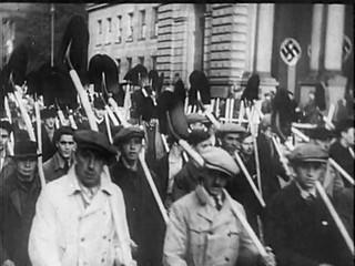 Marschierende Menschenmasse mit Hakenkreuz im Hintergrund