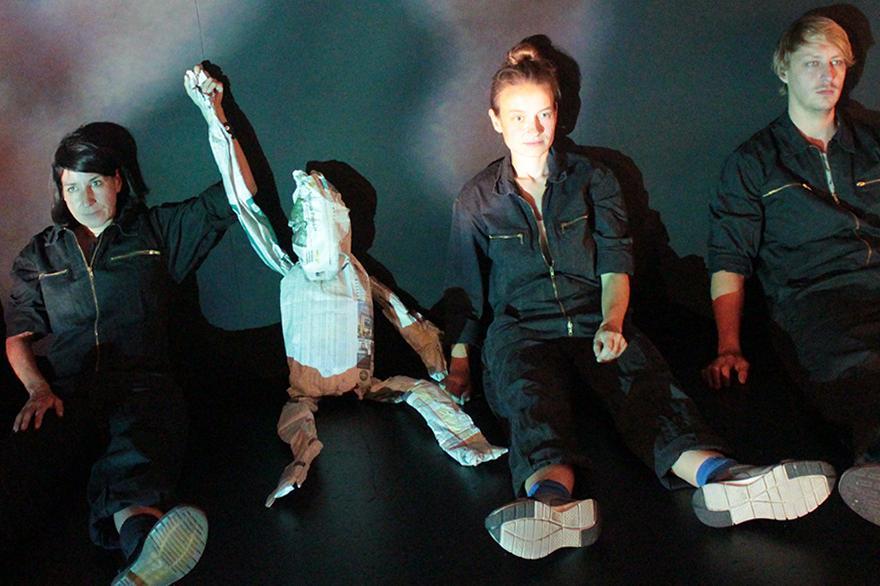 Schauspielende sitzen auf dem Boden.