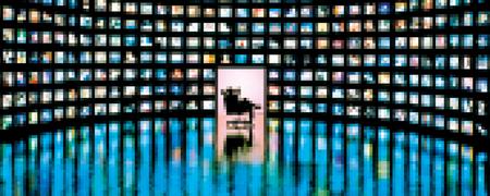 Ein Raum, dessen Wände von Bildschirmen bedeckt sind. Eine Person betrachtet diese Bildschirme.  - Link auf: Sie wissen alles