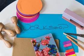 Das Bild zeigt ein Papier mit dem Wort Workshop sowie diverse Büroutensilien.