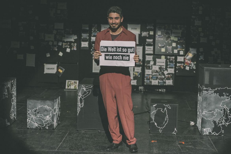 """Schauspieler hält Schild """"Die Welt ist so gut wie noch nie."""""""