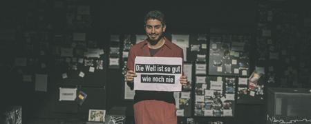 """Schauspieler hält Schild """"Die Welt ist so gut wie noch nie.""""  - Link auf: Theaterstück """"Revolution: Alles wird gut!"""""""
