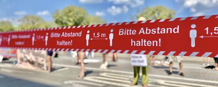 """Rotes Absperrband bei Demonstration mit Hinweis """"Bitte Abstand halten""""  - Link auf: Kommunen gegen globale Krisen"""