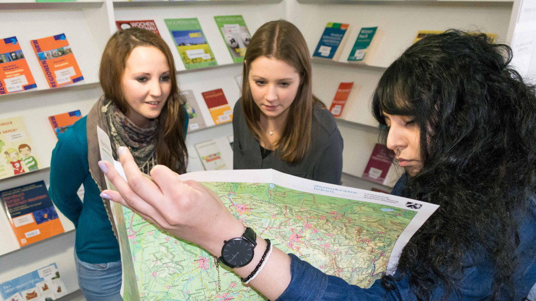 Drei Frauen schauen auf eine Landkarte