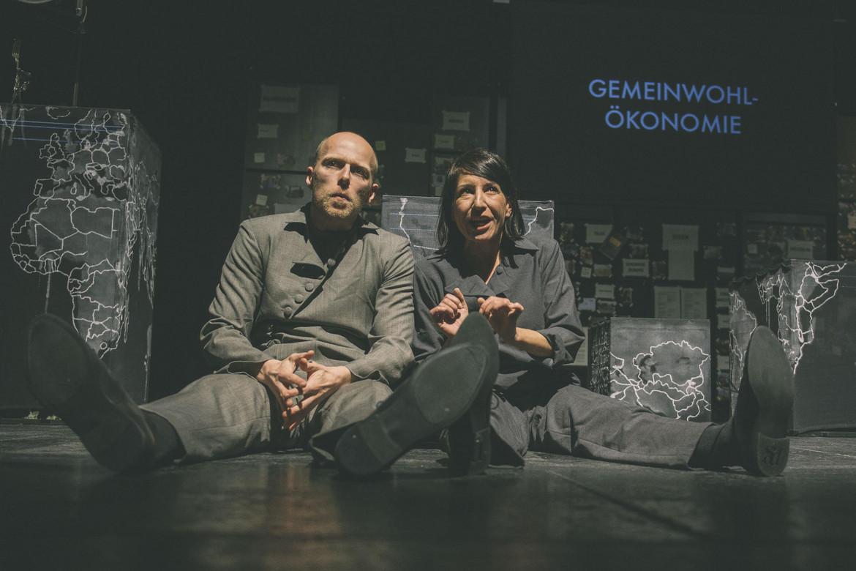 Schauspielende sitzen auf der Bühne.