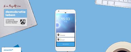 Mittig liegt ein Smartphone auf blauem Untergrund, am Bildrand zu erkennen ein Heft, eine Tasse Kaffe und eine Tastatur
