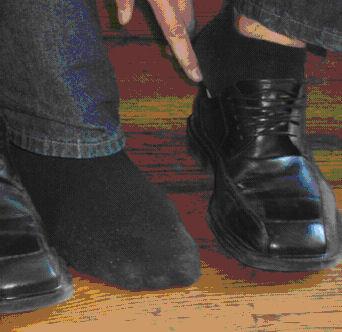 Ein Fuß mit Schuh und einer ohne.