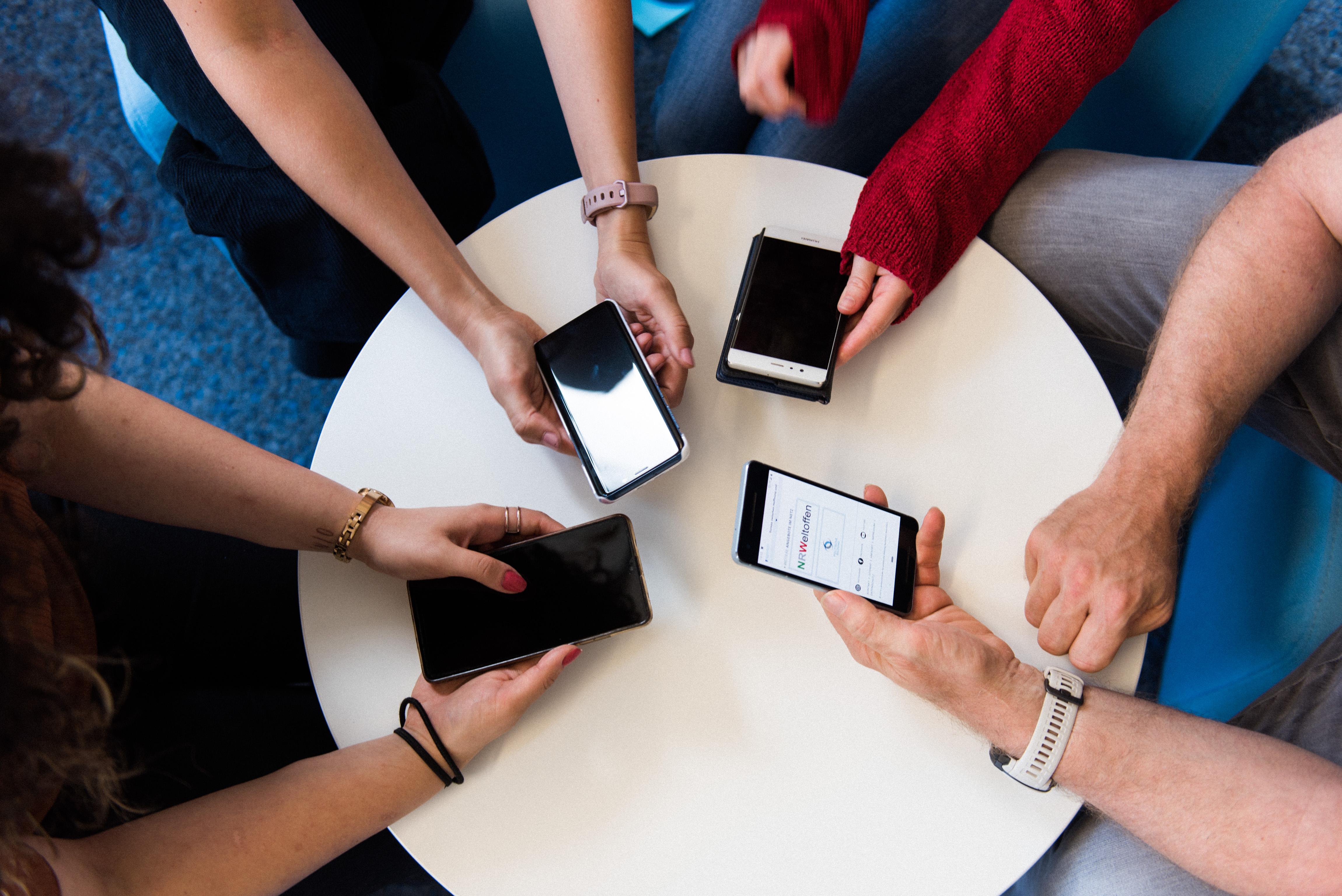 Das Bild zeigt einen Tisch von oben sowie vier Armpaare mit vier Smartphones.
